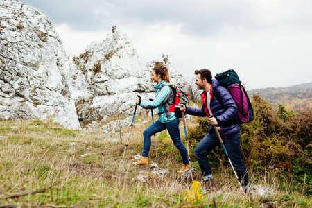 Glückliches Paar mit Rucksäcken wandern bergauf mit Steinen in backgorund Standard-Bild - 53938954