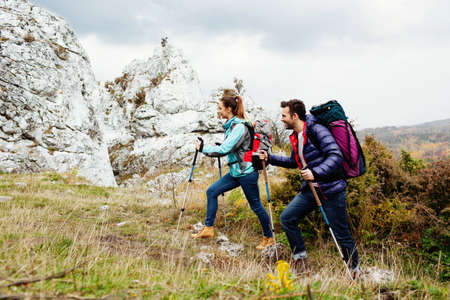attractive male: Happy couple with backpacks hiking uphill with rocks in backgorund
