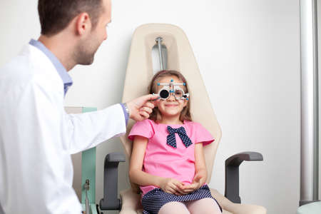 medical attendance: Young girl at the optometrist, optician. Stock Photo