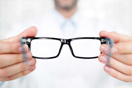 Close-up van optometrist, opticien giving glazen om te proberen