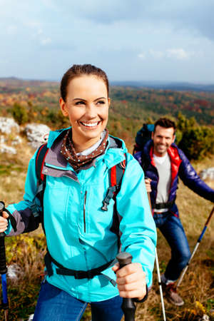 Young woman hiking with friend. Autumn travel. Foto de archivo
