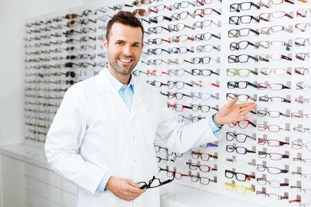 eye doctor: Optician selling glasses. Eye doctor, optometris at work. Stock Photo