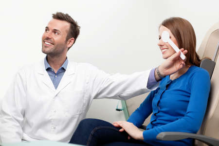 medical attendance: Eye exam of happy young woman performed by optometrist Stock Photo