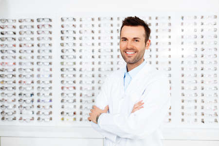 Confident optometrist, optician standing in store