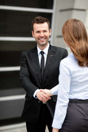 business person: Mid adult businessman shaking hand with businesswoman.