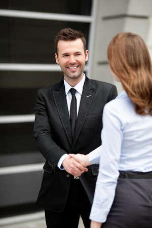 Mid volwassen zakenman schudden hand met zakenvrouw. Stockfoto