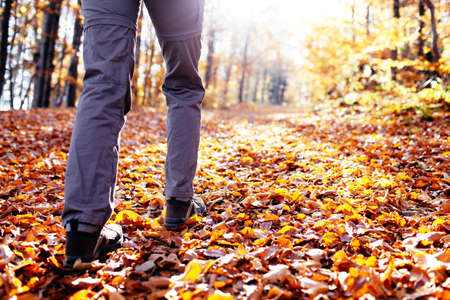 Autumn hiking. Close up of female walking uphill with lots of leaves around