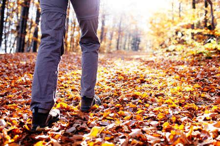 otoño de senderismo. Cerca de las mujeres caminar cuesta arriba con un montón de hojas alrededor