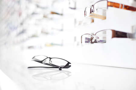 optical: Closeup of glasses with many eyeglasses in background