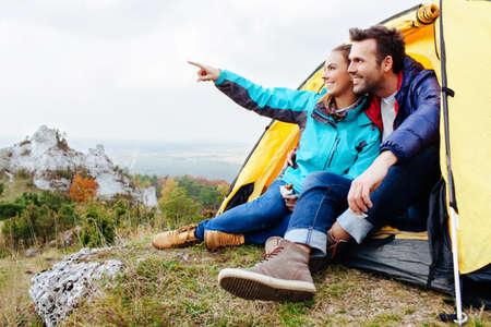 Echtpaar camping. Jonge mensen zitten in tent kijken naar de mening Stockfoto