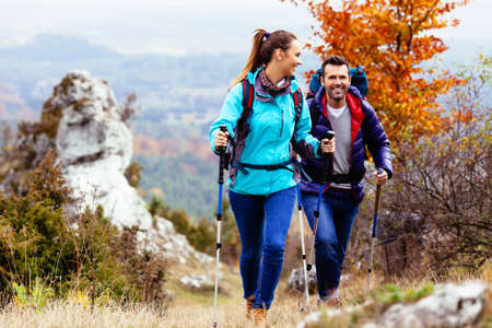 Woman and man hiking in mountains with backpacks Stock Photo