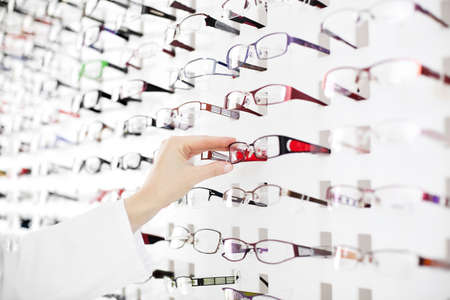 glasses eye: Optician suggest glasses. Closeup showing many eyeglasses in background.