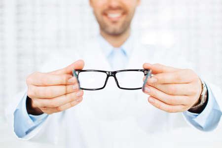 New glasses. Closeup of optician, optometrist giving eyeglasses to try Foto de archivo