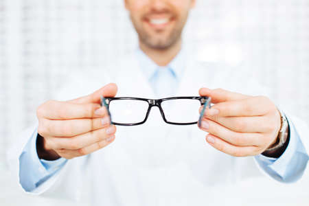 eye care professional: New glasses. Closeup of optician, optometrist giving eyeglasses to try Stock Photo