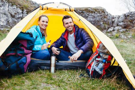 テントの中で座っているカップル。岩の近くでキャンプ