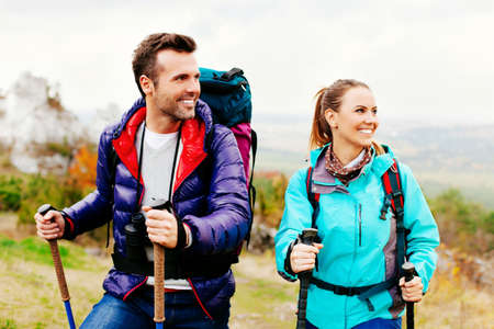 Happy couple hiking in mountains.