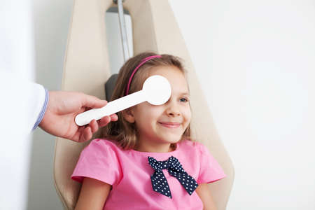 medical attendance: Young girl is having eye exam performed by optician, optometrist or eye doctor. Stock Photo