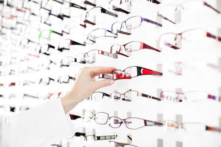 optician: Optician suggest glasses. Closeup showing many eyeglasses in background.
