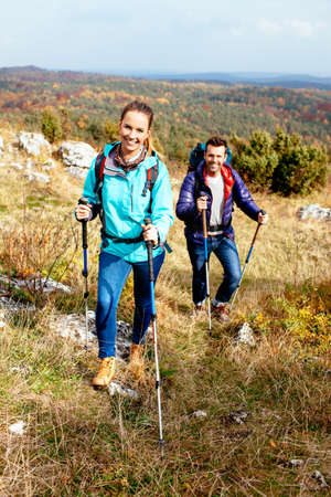 Young couple hiking in nature with sticks. Nordic walking