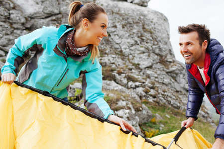 put up: Couple assembling a tent