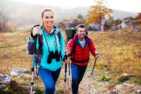 Backpacs や山の棒で幸せなカップルのハイキング