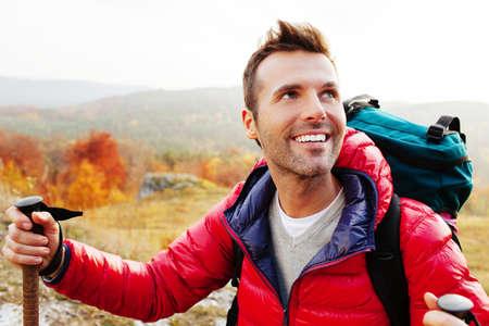 Glücklicher junger Mann mit Rucksack Wandern