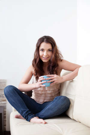 woman young: Beautiful young woman sitting on couch holding coffee cup