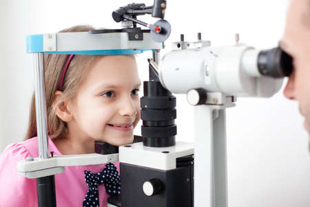eye exam: Young girl patient is having a medical attendance at the optometrist.
