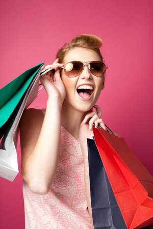fashionable sunglasses: Happy woman with shopping bags screaming. Isolated on pink
