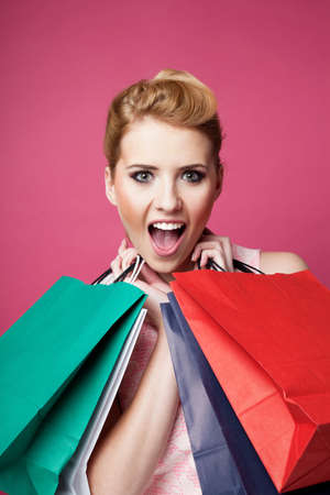 happy shopping: Happy woman with shopping bags screaming. Isolated on pink