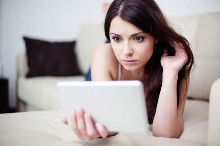 couch: Sad woman lying on couch with tablet Stock Photo