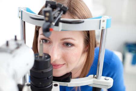 eye doctor: Young woman is having eye exam performed by eye doctor