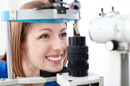 medical attendance: Young woman is having eye exam performed by optometris