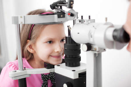 medical attendance: Optometrist performing visual field test of young girl Stock Photo