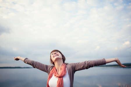 Felice giovane donna con le braccia alzate, outdor.