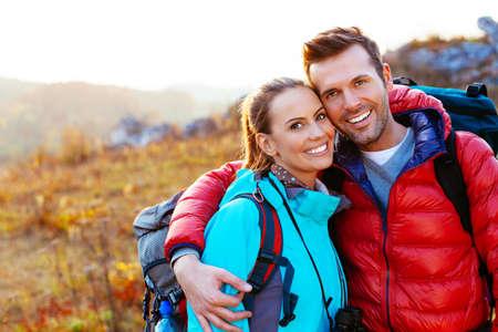 parejas: Pareja joven sonriendo en las montañas Foto de archivo