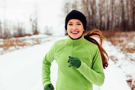 Gelukkige jonge vrouw die in de winter loopt