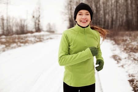 Happy woman running in winter Reklamní fotografie