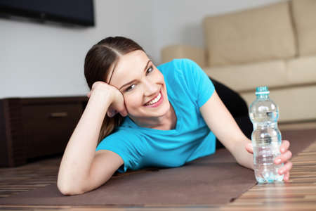 Happy young woman lying on the floor with bottle of water after yoga exercises