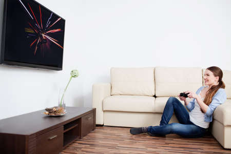 adult entertainment: Young woman playing video games in living room Stock Photo
