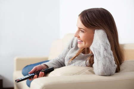 Glückliche junge Frau vor dem Fernseher auf dem Sofa