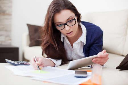 若い女性が彼女のデジタル タブレットを使用して自宅から働いて