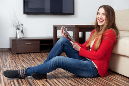 jean: Happy young woman with tablet in living room
