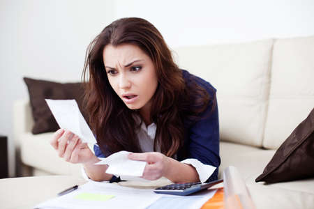 accounts: Desperate young woman calculating bills in living room