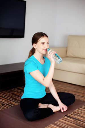 joga: Young woman drinking water after joga exercises in living room. Stock Photo
