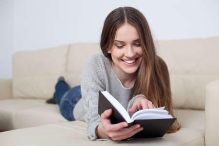Pretty young woman reading book on sofa