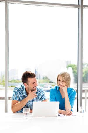 personas hablando: conceptos de trabajo en equipo. Pareja feliz trabajando juntos en la computadora portátil en la oficina. Foto de archivo