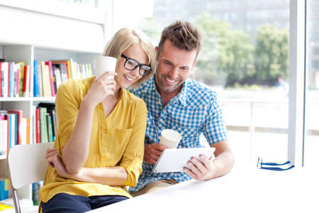 Couple in library working with digital tablet and drinking coffee