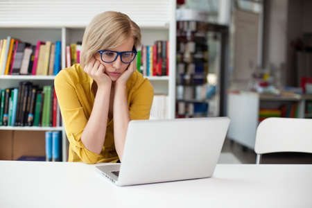 work from home: Overworked female student working in library Stock Photo
