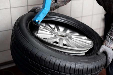 llantas: Primer plano mecánico de cambiar los neumáticos de coches